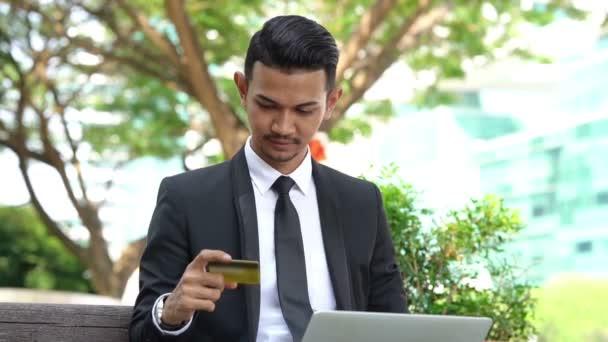 Boldog ázsiai üzletember ujjongott, kéztároló hitelkártya ül laptop kültéri.