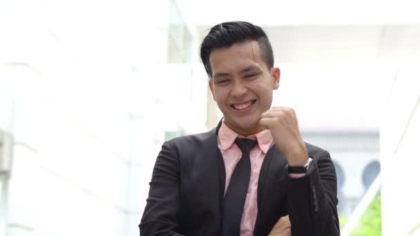 junger Geschäftsmann lächelt fröhlich im Freien, feiert Erfolg, urbaner Hintergrund.