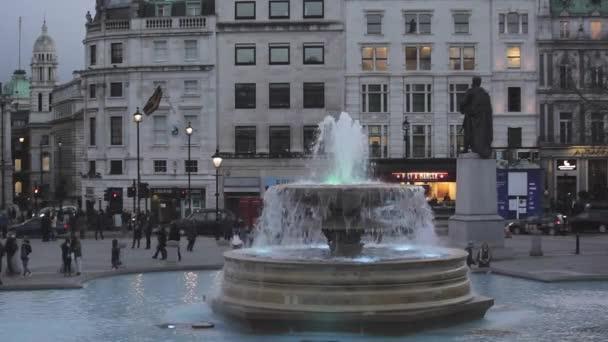 Londýn, Velká Británie - 27. ledna 2013: Fontána na Trafalgar Square Zimní večer s turisty v Londýně, Velká Británie.