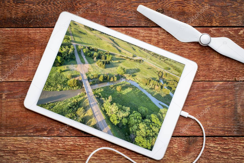 highway and bridge over the Dismal River in Nebraska Sandhills, reviewing an aerial image on a digital tablet