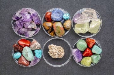 set of polished, semiprecious, colorful gemstones with Gypsum rosette (desert rose) in round bowls against a slate stone
