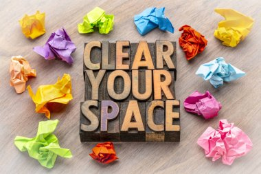 clear your space concept - word abstract in vintage letterpress wood type with crumpled notes