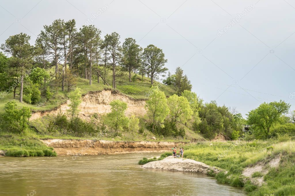 Norden, NE, USA - May 27, 2018:  Niobrara River below Norden bridge with a group of people in conversation on a beach.