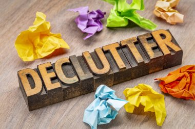 declutter - abstract in vintage letterpress wood type blocks with crumpled sticky notes