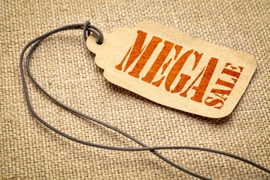 mega sale sign - a paper price tag with a twine iagainst burlap canvas