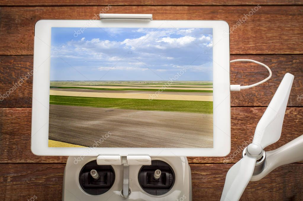 rural Nebraska landscape with wheat, corn and plowed fields - reviewing an aerial image on a digital tablet mounted on a drone radio controller