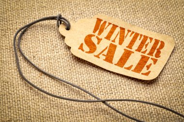 winter sale sign - red stencil text on a paper price tag against burlap canvas