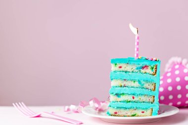 Colorful slice of birthday cake with one candle