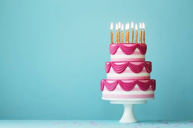 Tiered birthday cake with golden candles