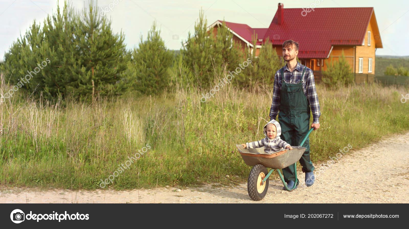 Father Working Uniform Pushing Son Wheelbarrow Rural Road
