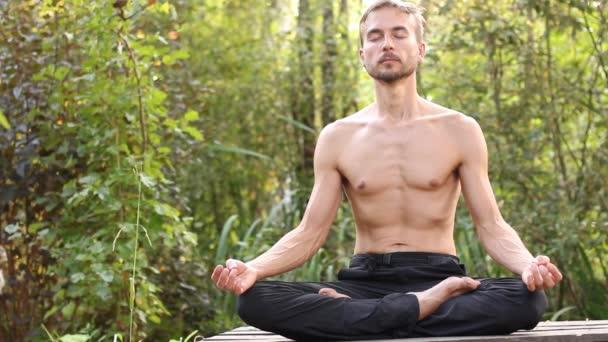 Mladý vousatý muž sedící v póze Lotus se zavřenýma očima. On dech hluboce, pak otevřít oči, s úsměvem a rozhlédněte se kolem sebe. Zelený les na pozadí. Jóga na pojetí přírody.