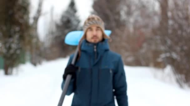 Portrait of a handsome bearded man in casual clothes with snow shovel, standing on a snowy rural road on cold winter day. Season concept.
