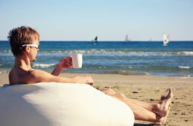 Male surfer in sunglasses resting on pouf on beach with cup of t