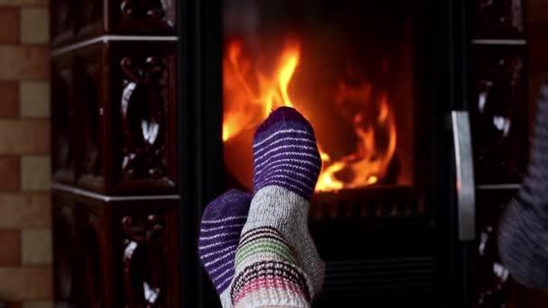Relaxační krbu. Žena a muž nohy vlněné ponožky, oteplování před ohněm. Zimní sezóna koncept.