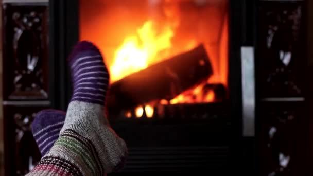 Woman feet in wool socks warming by fireplace. Winter season concept.