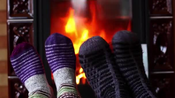 Man and woman feet in woolen knitted socks dance by the fireplace. Winter season concept.