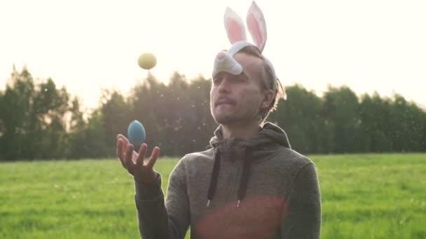 Vicces felnőtt férfi nyuszi füle juggles színes festett tojások zöld tavaszi gyep a természetben vagy Park. Húsvéti ünnepség koncepciója. Lassított mozgás.