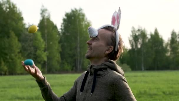 Húsvéti ünnepség koncepciója. Vicces felnőtt férfi nyuszi füle juggles színes tojás tavasszal Park.