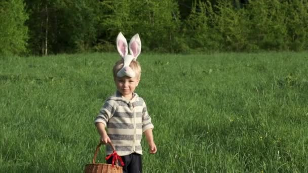 Easter egg hunt. Cute little kid in bunny mask with basket with eggs jumps up like rabbit. Slow motion.