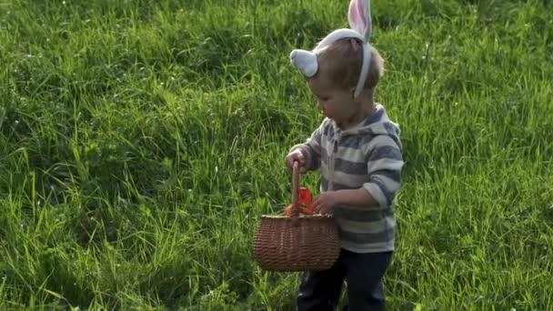 Imádnivaló kisgyermek gyerek nyuszi füle a húsvéti tojás vadászat az ő kosarat a kertben vagy a parkban. Húsvét ünnepe. Lassított mozgás.