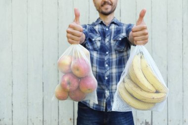 Happy smiling adult man holding reusable eco bags with fresh fruits and showing LIKE sign. Zero waste shopping, ban single use plastic concept.