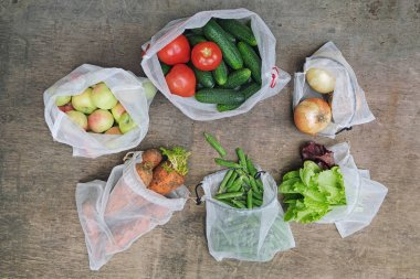Zero waste shopping concept. No single-use plastic. Fresh organic vegetables, fruits and greens in reusable recycled mesh produce bags on wooden background. Flat lay.