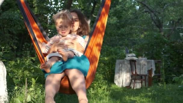 Mutter und Sohn ruhen sich im orangefarbenen Hängemattenstuhl in der Natur am Sonnenuntergang aus, Gartentisch im Hintergrund. Mutter und Kind im Sommerurlaub im Dorf. Cottagecore, langsames Leben auf dem Land. Zeitlupe.