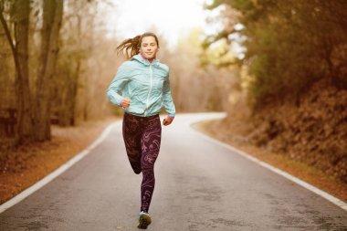 girl running on an asphalt road
