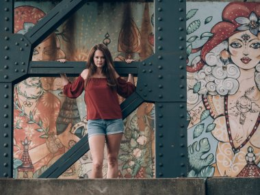 Fashionable young woman standing by graffiti wall