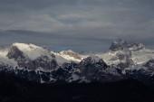 Fotografie Zasněžené horské pásmo. Triglav pod mraky. Julské Alpy,