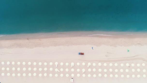 Letecký pohled shora na pláži. Deštníky, písek a mořské vlny. Pracovní písek čistící stroj