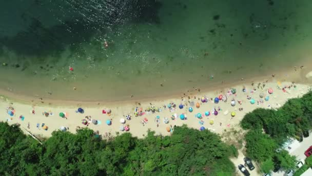 Aerial top view on the beach. Umbrellas, sand and sea waves. Summer holidays.