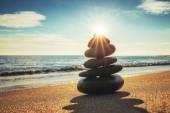 Fotografie Steinen Gleichgewicht am Strand, Sonnenaufgang erschossen. Zen-Meditation, Yoga-Übungen.