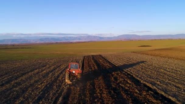 A légi felvétel a betakarítási területeken traktor. Mezőgazdasági termelő plowing tarló mező.
