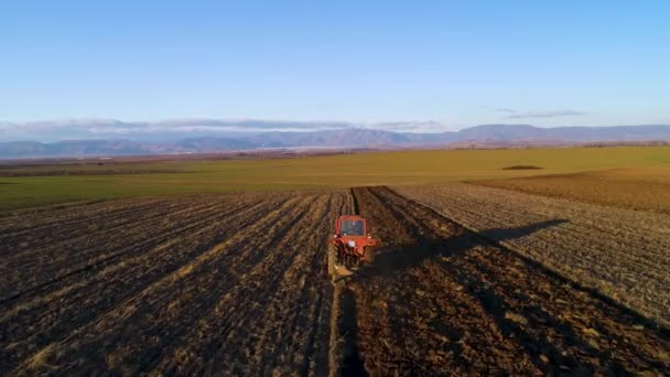 Aerial view of harvest fields with tractor. Farmer plowing stubble field.
