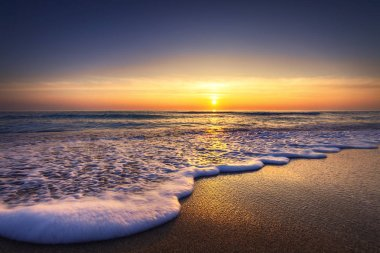 Sunrise over the sea and beach. Waves washing the sand.