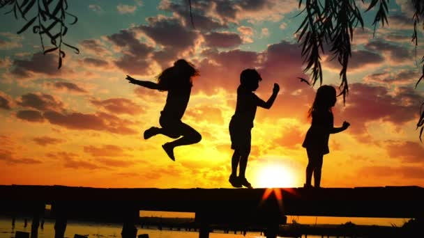 Sunset and silhouettes of happy kids jumping on the wooden pier above the lake water