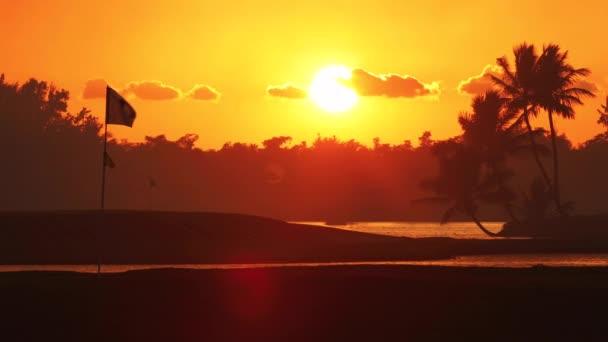 Golfové hřiště na tropickém ostrově, nádherný západ slunce s siluety palmových stromů