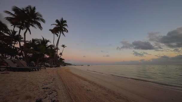 Sunrise over tropical island beach in Punta Cana, Dominican Republic. Tractor cleaning the sand