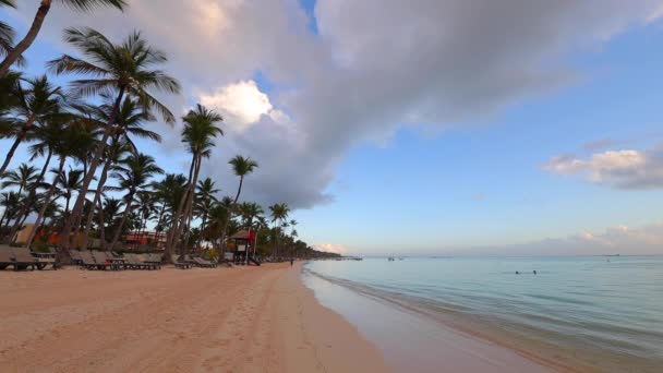 Napfelkeltét a trópusi szigeten strand és pálmafák felett. Punta Cana, Dominikai Köztársaság.