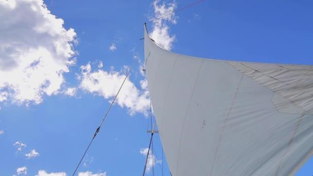 Plachty Plachetní lodi v Karibském moři proti slunečným nebesům