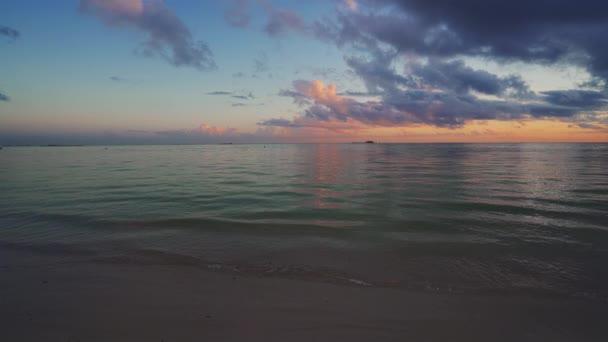 Tropical beach and caribbean sea at sunrise. Waves splashing on the sea sand