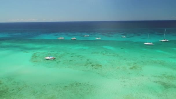 Aerial view over Caribbean sea water. Catamaran and speed boats in the ocean.