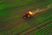 Tractor cultivating field at spring, aerial sunset view