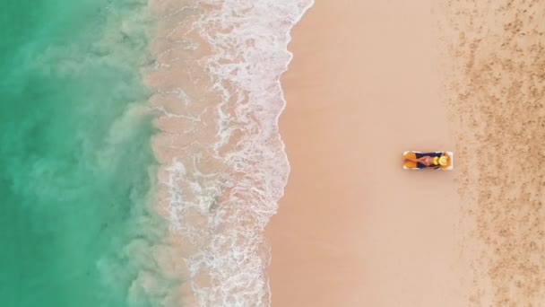 Beach vacation in paradise tropical island, sexy suntan woman relaxing on idyllic summer background in clear water and beach. Top view aerial drone video.