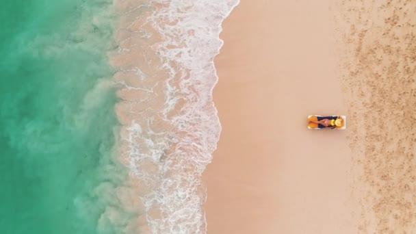 Tengerparti vakáció a Paradise Tropical Island, szexi naptan nő pihentető idilli nyári háttér tiszta víz és a strand. Felülnézet antenna drone videó.