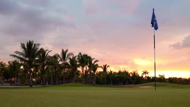 Horizont golfového hřiště. Západ slunce nad sportovními poli, pozemky a palmami