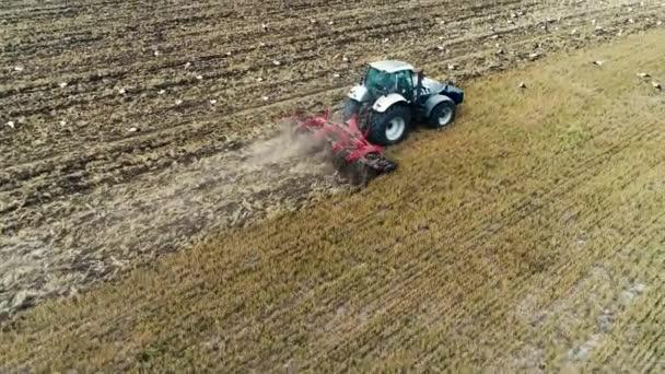 Traktor a napájecí čápy na poli, letecká zemědělská krajina