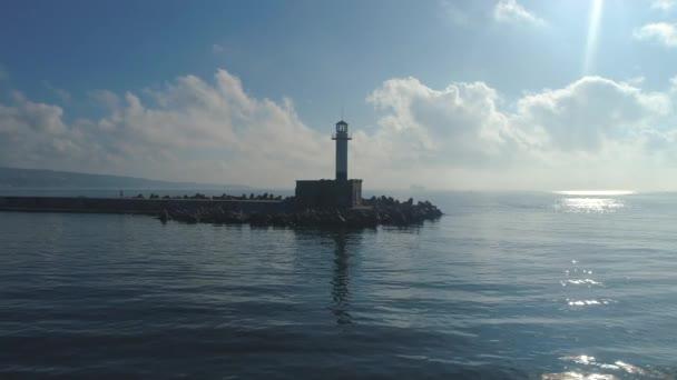 Maják v moři při východu slunce a zářících vlnách