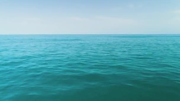 Oceánské vlny zblízka, nízký úhel pohledu. Východ slunce nad tyrkysovou mořskou vodou.